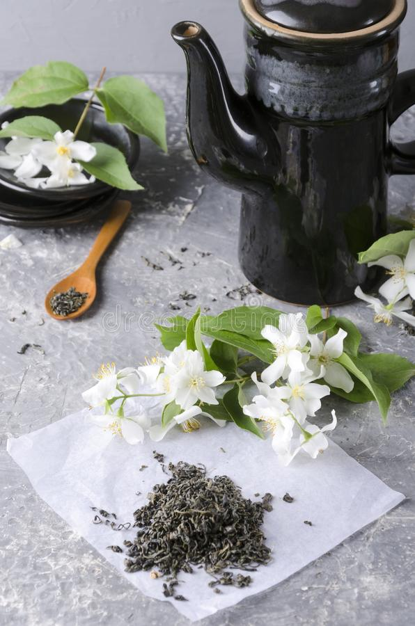 Vertical shot.Black teapot,plates and spoon, jasmine flowers and heap of green tea on the grey table.Concept of tea time royalty free stock image