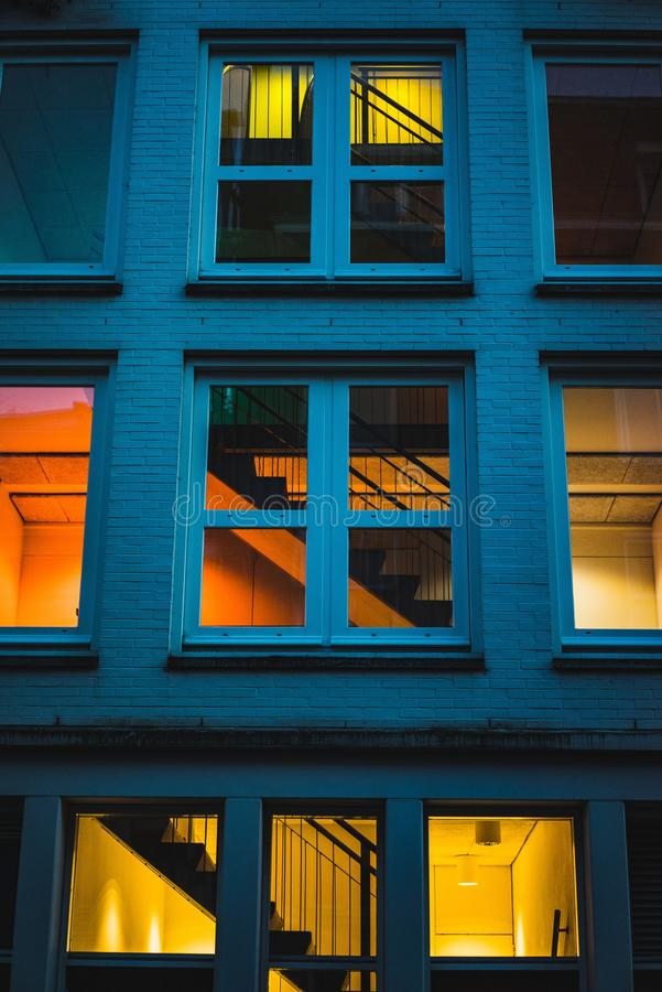 Vertical shot of a blue building with big windows lit up from the inside royalty free stock photo