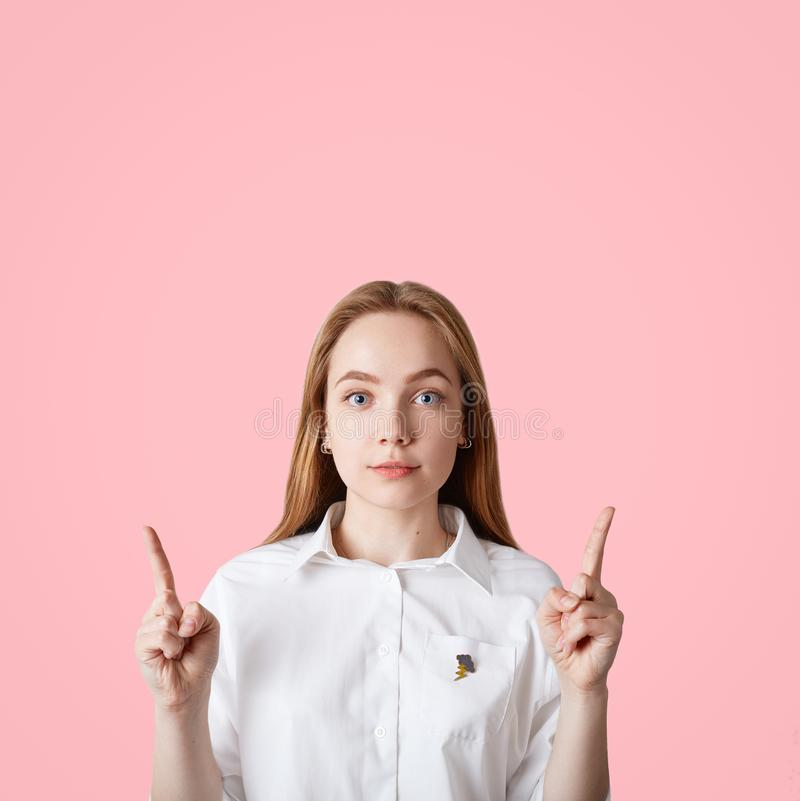 Vertical shot of blue eyed female with healthy skin, keeps fore fingers raised upwards, shows copy space for your promotional text stock images