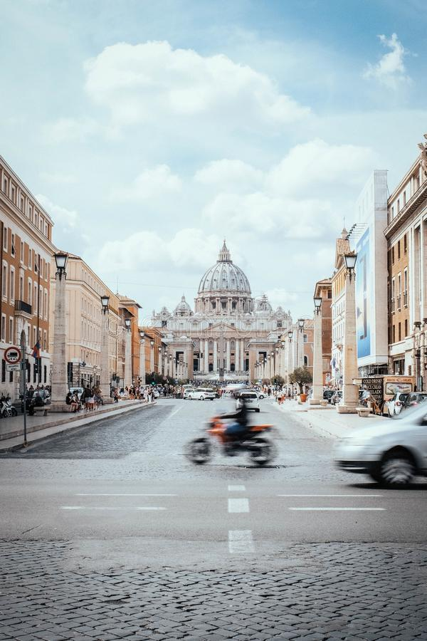 Vertical shot of a blurred motorbiker and the St. Peter`s Basilica in Vatican City. A vertical shot of a blurred motorbiker and the St. Peter`s Basilica in stock images