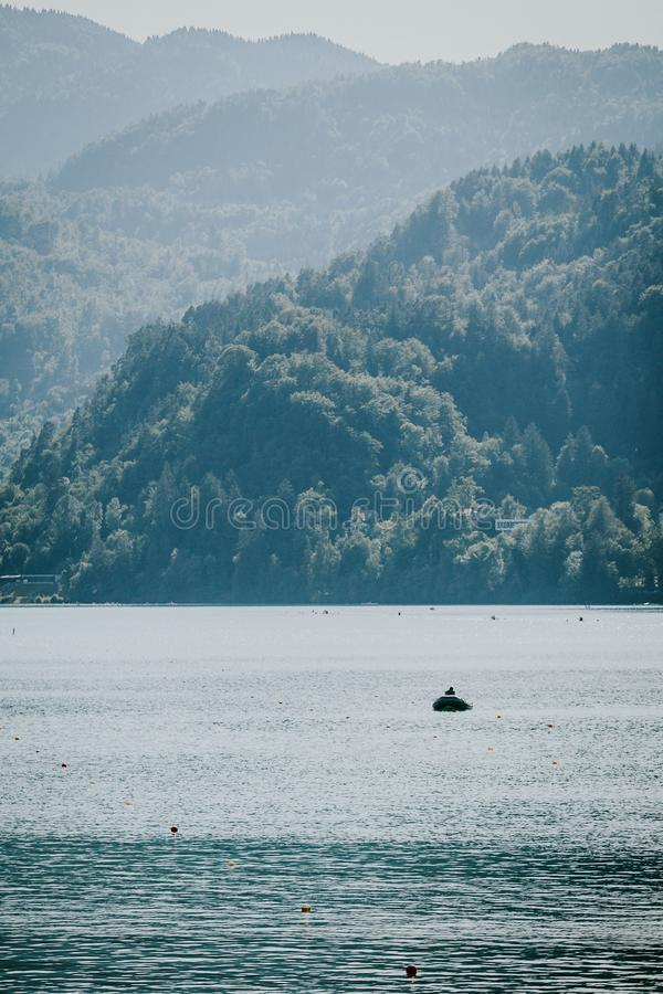 Vertical shot of a boat on the water with forested mountains in the background. A vertical shot of a boat on the water with forested mountains in the background stock photography