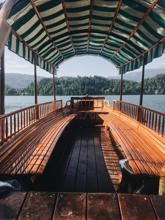 Vertical shot of a boat with a wooden seat and floor on the water. A vertical shot of a boat with a wooden seat and floor on the water stock image