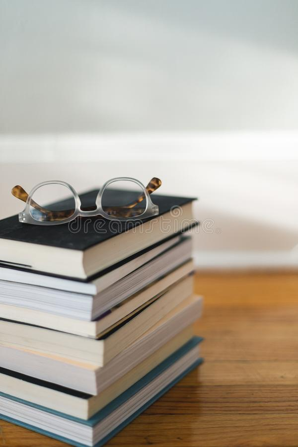 Vertical shot of books placed on one another with glasses at the top. A vertical shot of books placed on one another with glasses at the top stock images