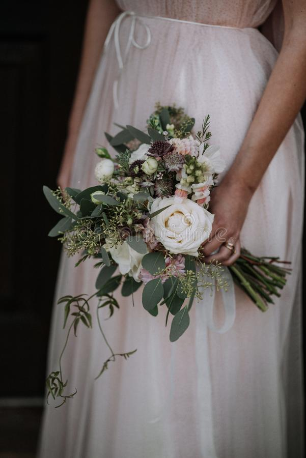 Vertical shot of a bride wearing wedding dress holding a flower bouquet. A vertical shot of a bride wearing wedding dress holding a flower bouquet stock photo