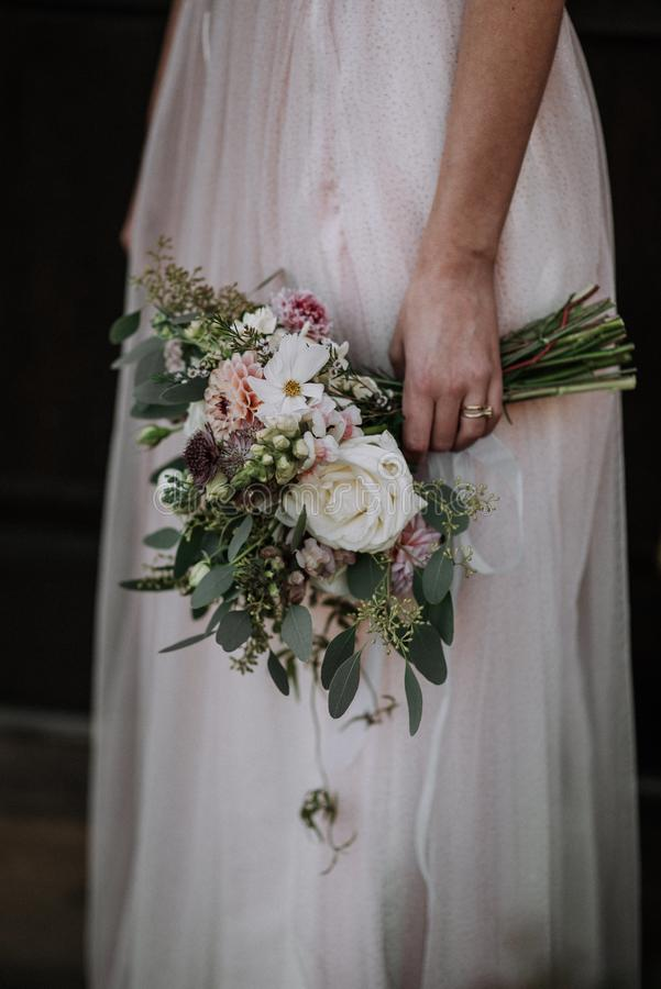 Vertical shot of a bride wearing wedding dress holding a flower bouquet. A vertical shot of a bride wearing wedding dress holding a flower bouquet stock image
