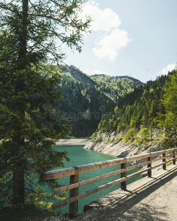Vertical shot of a bridge with a wooden fence above the water near forested mountains at daytime. A vertical shot of a bridge with a wooden fence above the water stock image
