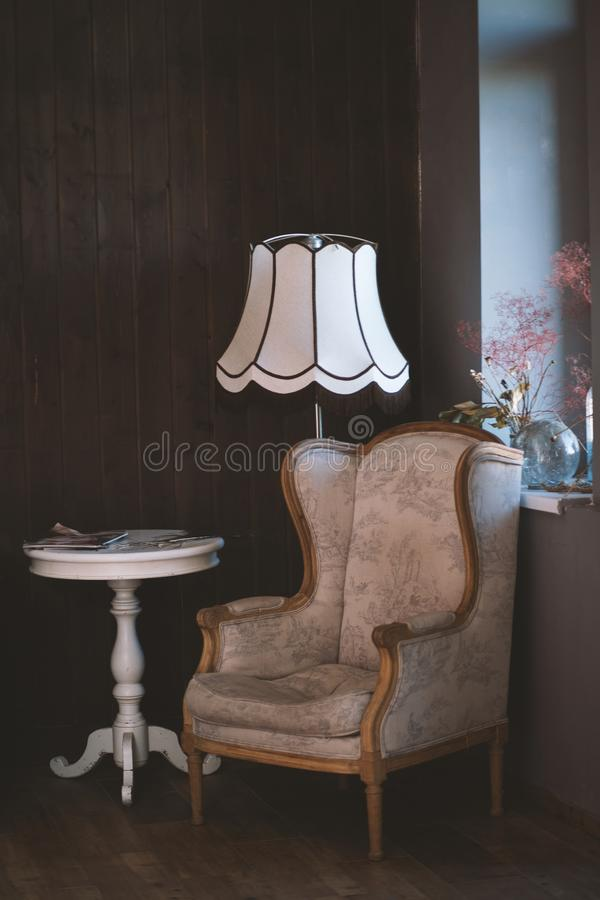 Vertical shot of a brown armchair near a white round table and a lamp. A vertical shot of a brown armchair near a white round table and a lamp royalty free stock photo