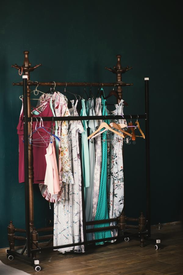 Vertical shot of brown clothes hangers and colorful clothes hanged on a rack. A vertical shot of brown clothes hangers and colorful clothes hanged on a rack stock image
