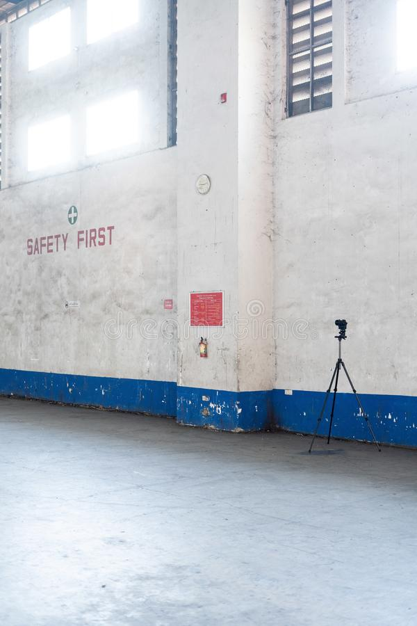 Vertical shot of a camera on a tripod in a factory near white walls stock photo