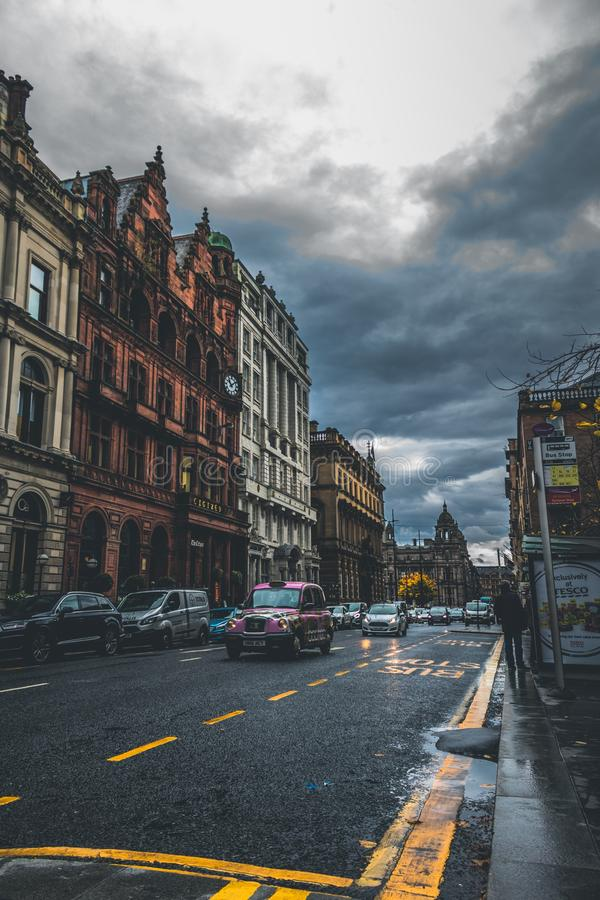 Vertical shot of cars on a street near brown and white buildings in Glasgow, UK. A vertical shot of cars on a street near brown and white buildings in Glasgow royalty free stock image