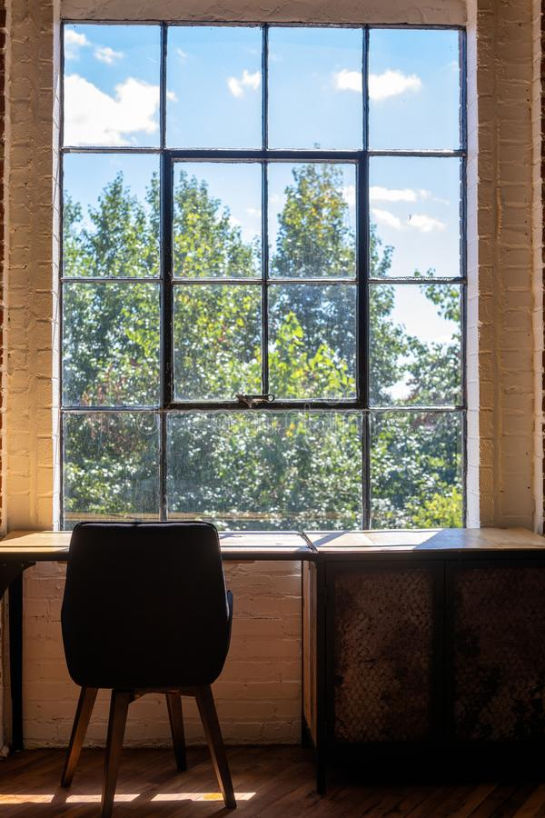 Vertical shot of a chair and a desk near a large window with an amazing view of greenery outside. A vertical shot of a chair and a desk near a large window with stock images