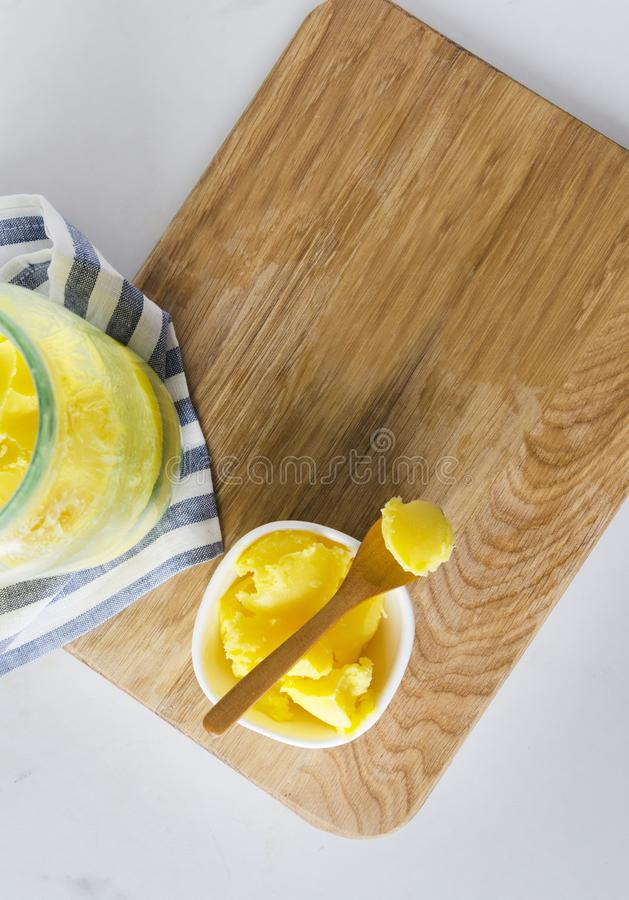 Vertical shot. Chee or clarified butter on the kitchen table,empty space. Top view of bowl and jar with ghee or clarified butter on chopped board. Healthy eating stock photos