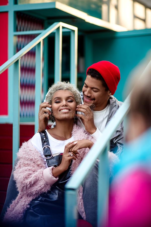 Vertical shot of cheerful man in trendy hat puts on headphones to his mulatto female friend, have entertainment together royalty free stock images