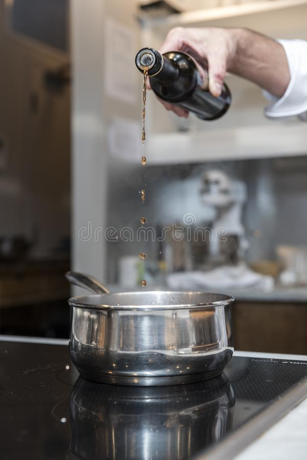 Vertical shot of a chef`s hand pouring liquid into a cooking bowl. A vertical shot of a chef`s hand pouring liquid into a cooking bowl royalty free stock photo