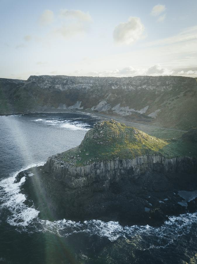 Vertical shot of a cliff by the water under a clear sky with clouds. A vertical shot of a cliff by the water under a clear sky with clouds stock image