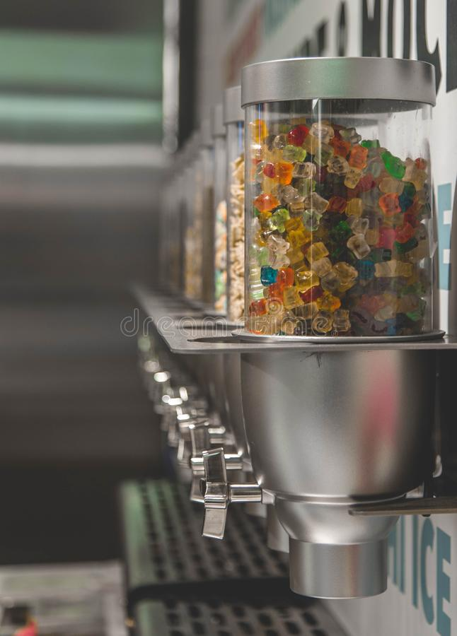 Vertical shot of colorful gummy candies inside of a dispenser. A vertical shot of colorful gummy candies inside of a dispenser stock images