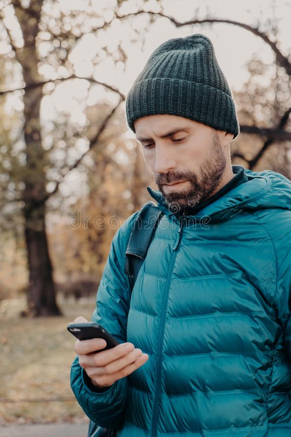 Vertical shot of concentrated hipster guy with thick beard, wears anorak and hat, holds cellular, uses special application for. Finding route, message with stock photos
