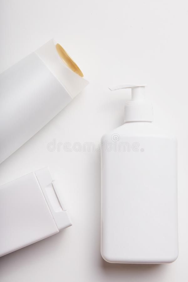 Vertical shot of cosmetic bottles with empty space for your design or promotion. Beauty products. Skin care. Shampoo, gel and soap stock image