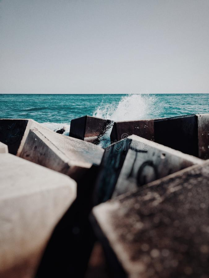 Vertical shot of cubical rubbles and trash in the body of water in the ocean royalty free stock photo