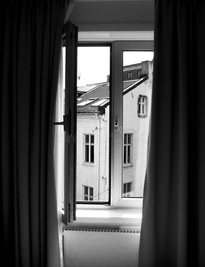 Vertical shot of curtain and open window with a view of the building in black and white. A vertical shot of curtain and open window with a view of the building stock photo