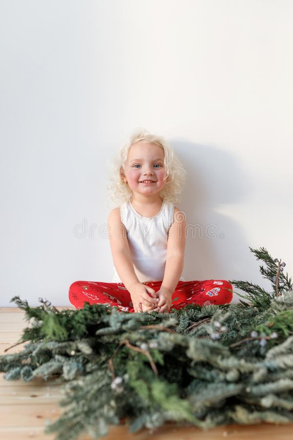 Vertical shot of cute lovely small girl sits crossed legs against white background, has happy expression, rejoices stock photography