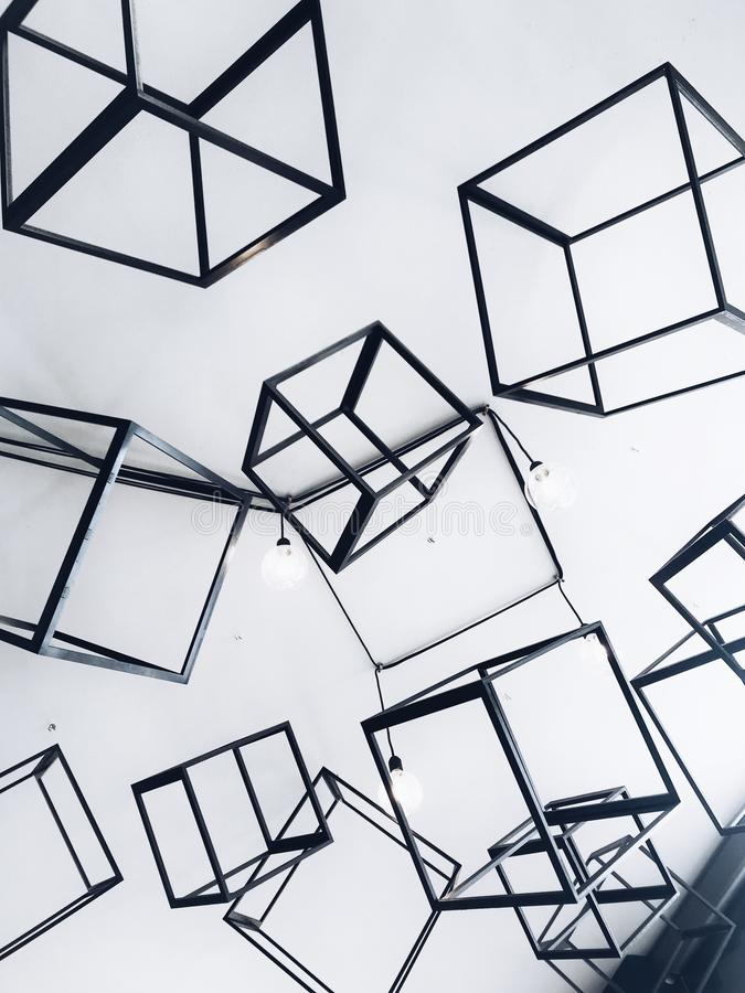 Vertical shot of decorative grey metal cubes in a white room - perfect for interior design blogs. A vertical shot of decorative grey metal cubes in a white room stock photo