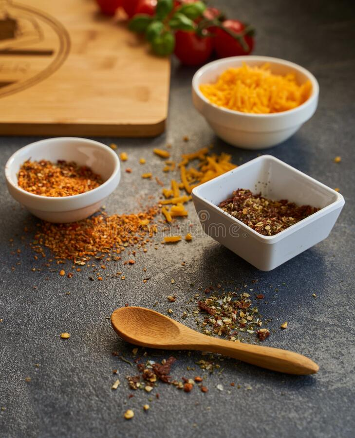 Vertical shot of different seasonings in bowls next to a wooden spoon and a chopping board. A vertical shot of different seasonings in bowls next to a wooden royalty free stock photos