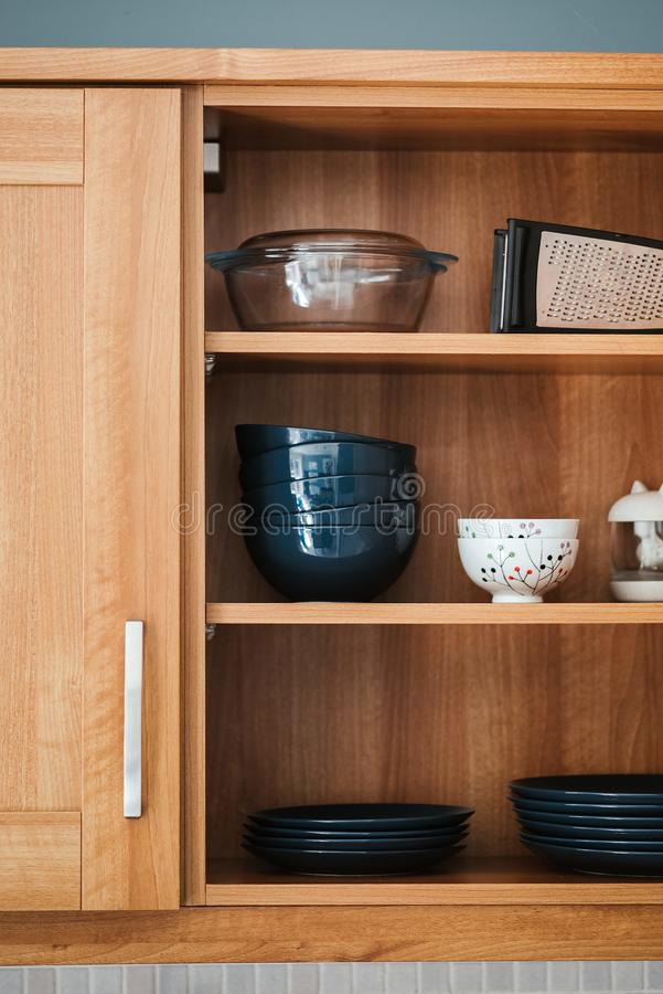 Vertical shot of dishware in a wooden crockery cabinet. A vertical shot of dishware in a wooden crockery cabinet royalty free stock photo