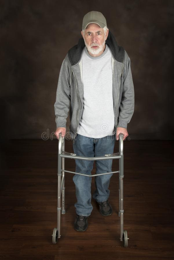 Elderly Man With Walker. Vertical shot of elderly man walking with the aid of a walker across a wooden floor. Brown background stock photos