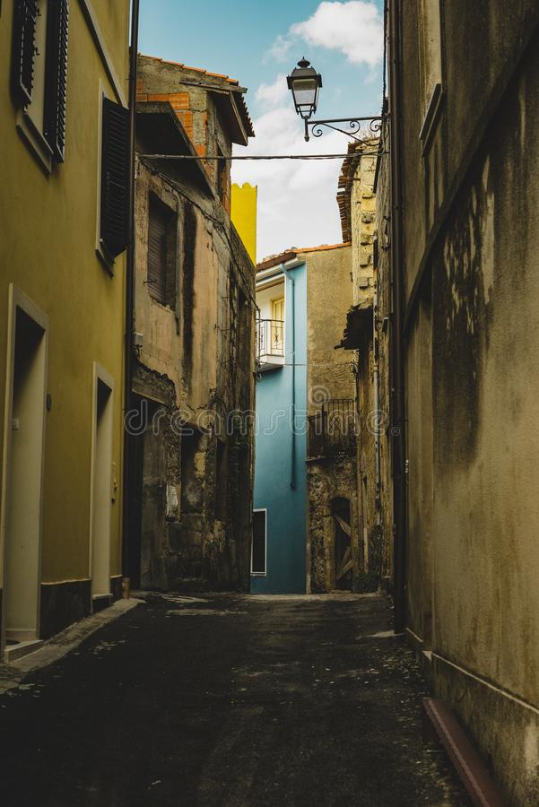 Vertical shot of an empty alley aligned with old yellow buildings leading to a blue building royalty free stock photos