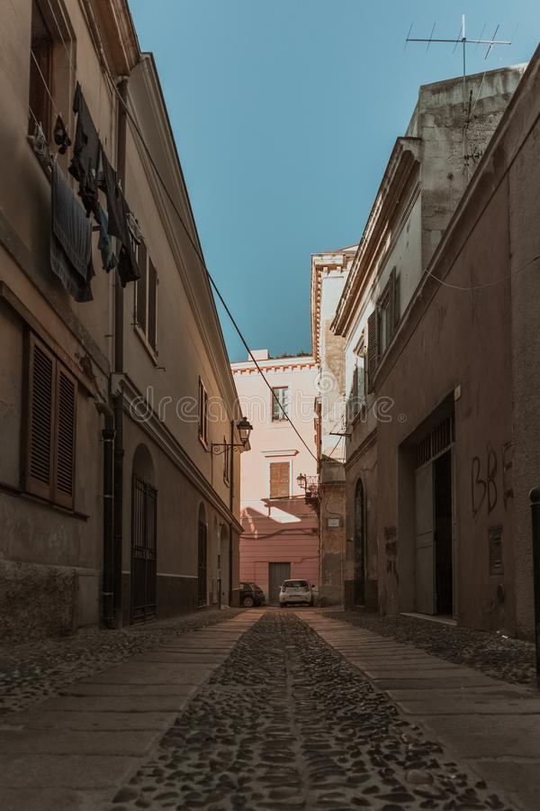 Vertical shot of an empty alleyway in the middle of buildings under a blue sky at daytime. A vertical shot of an empty alleyway in the middle of buildings under royalty free stock photo