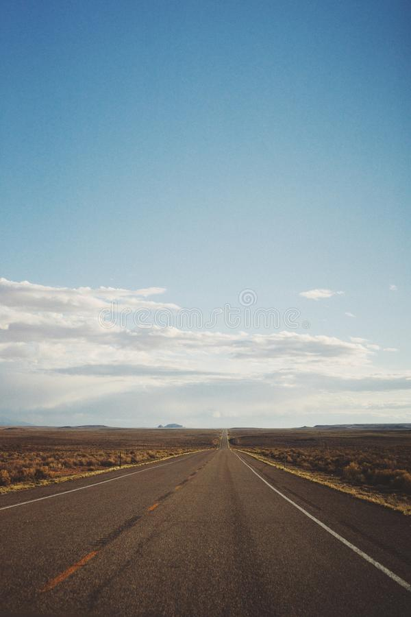 Vertical shot of an empty road in the middle of a desert under a beautiful blue sky stock photography