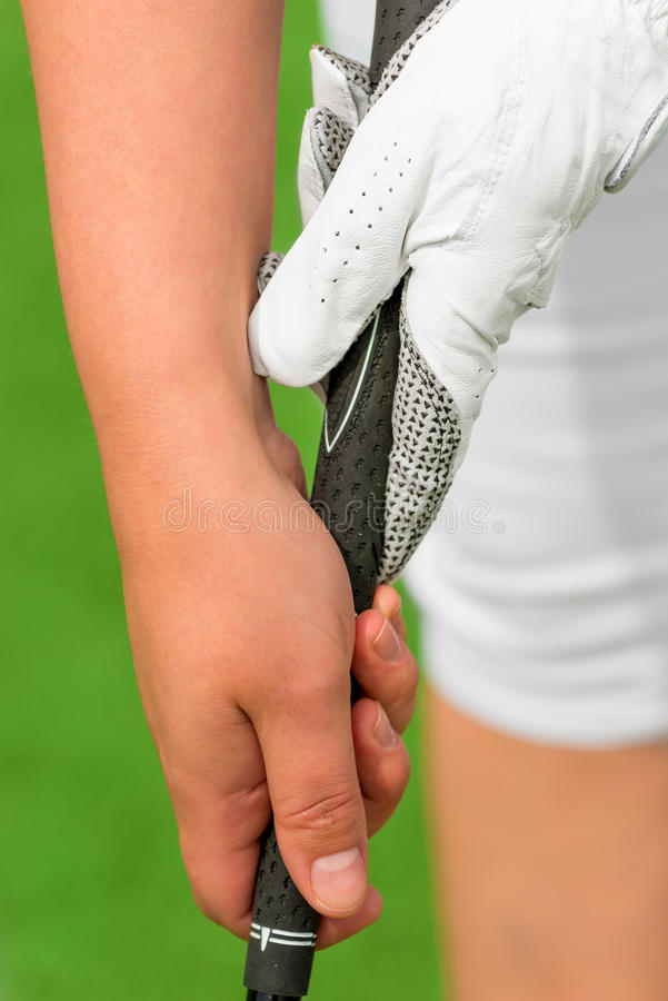 Vertical shot of female hands with a golf club. On the pitch royalty free stock images