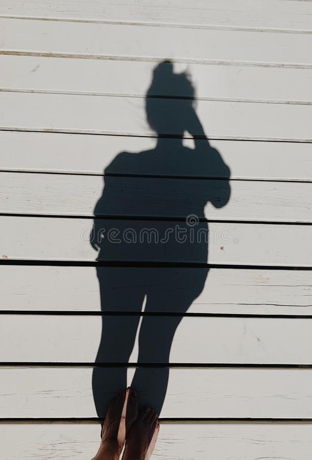 Vertical shot of a females feet and her shadow on a white wooden platform. A vertical shot of a females feet and her shadow on a white wooden platform stock photo