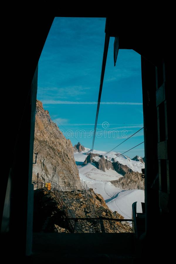 Vertical shot of a fenced pathway near mountains and ruth glaciers covered with snow. A vertical shot of a fenced pathway near mountains and ruth glaciers stock photo