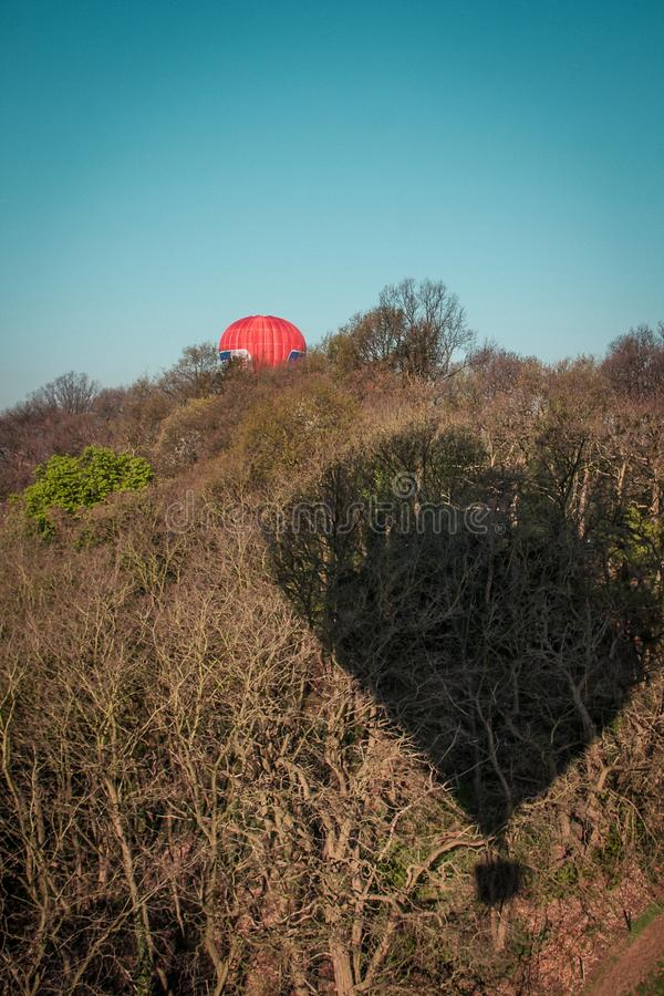 Vertical shot of a field with a hot air balloon in the air with its shadow on the hill stock photos