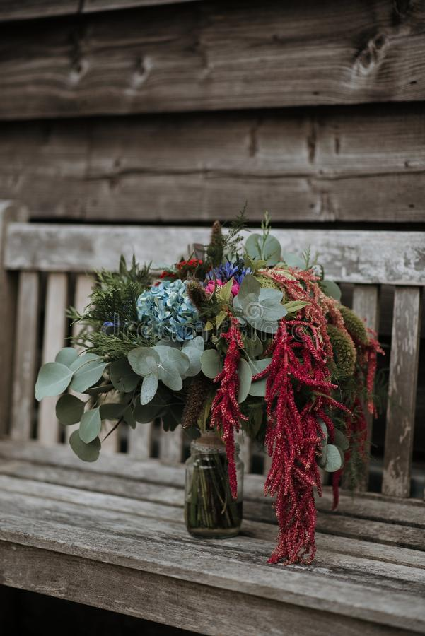 Vertical shot of a flower bouquet in a glass vase on a wooden bench. A vertical shot of a flower bouquet in a glass vase on a wooden bench royalty free stock photos
