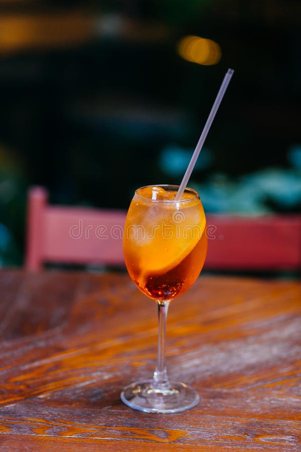 Vertical shot of fresh sweet aperol spiritz cocktail with slice of orange, on wooden table in cafe. Restaurant apertif drink. Summ. Er time concept royalty free stock photo