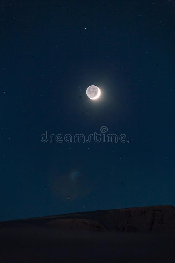 Vertical shot of the full moon in the sky full of stars at night time. A vertical shot of the full moon in the sky full of stars at night time royalty free stock images