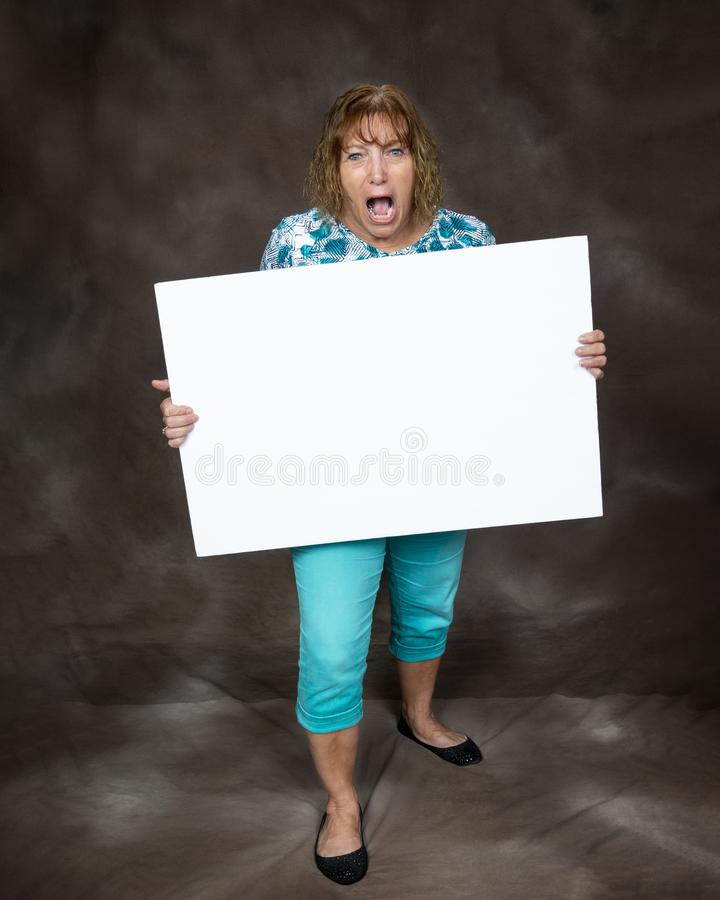 Furious Screaming Woman Holding Blank Sign. Vertical shot of a furious screaming woman holding a blank sign.  Brown background royalty free stock photography