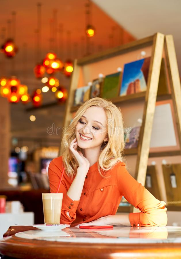 Vertical shot of girl sitting at table against. Designer with big blue eyes and blonde hair wears red shirt. Positive businesswoman has inspiration for work stock images