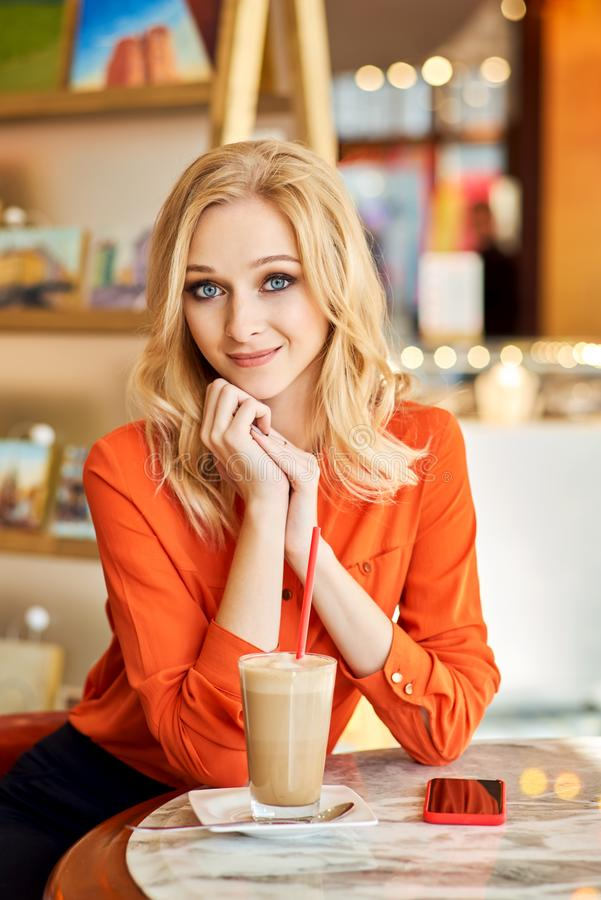 Vertical shot of girl sitting at table against. Designer with big blue eyes and blonde hair wears red shirt. Positive businesswoman has inspiration for work royalty free stock photography