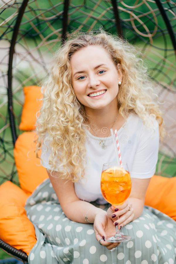 Vertical shot of good looking pretty young blonde female with curly hair, positive smile, spends free time with friends, have part. Y together, poses in hanging royalty free stock image