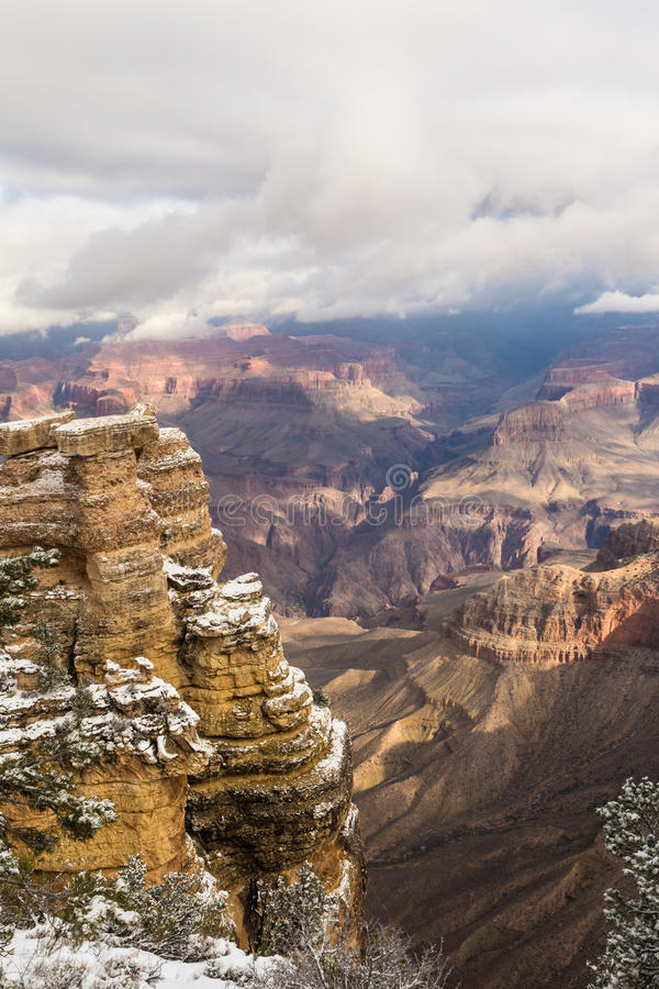 Vertical shot of the Grand Canyon. When the sun breaks through the clouds in the snowy weather royalty free stock photos