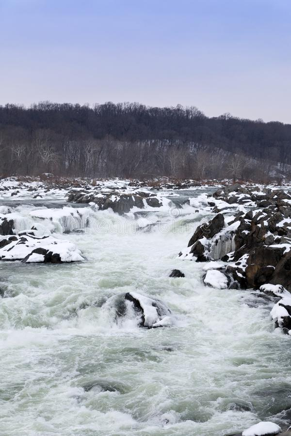 Vertical Shot of Great Falls in the Winter with Snow Covered Rocks royalty free stock image