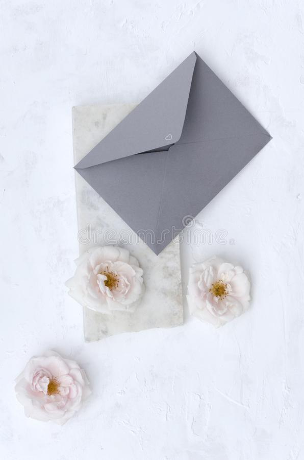 Vertical shot of grey envelope on the marble stone, pink soft roses on the white background. Top view of craft envelope, beautiful delicate roses, piece of royalty free stock photos