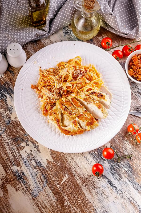 Vertical shot Grilled chicken fillet with spaghetti with tomato sauce on a white plate. Traditional Italian Mediterranean cuisine stock photos