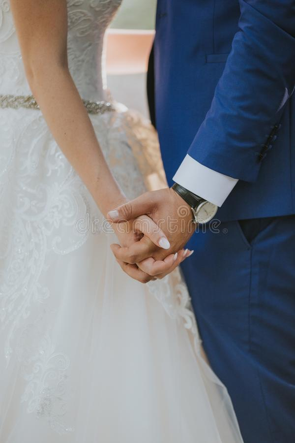 Vertical shot of the groom and the bride holding hands at the wedding ceremony. A vertical shot of the groom and the bride holding hands at the wedding ceremony royalty free stock image