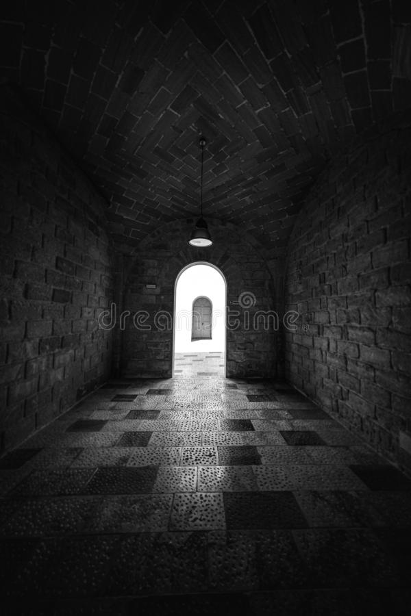 Vertical shot of a hallway with a doorway in the distance in black and white. A vertical shot of a hallway with a doorway in the distance in black and white royalty free stock photos