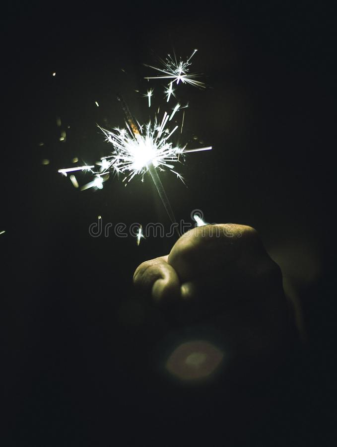 Vertical shot of a hand holding a sparkler on black background. A vertical shot of a hand holding a sparkler on black background stock photo